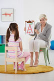 Speech therapist and small girl. With language problem stock image