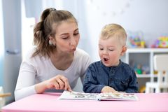 Speech therapist teaching letter pronunciation to kid boy in classroom royalty free stock photo