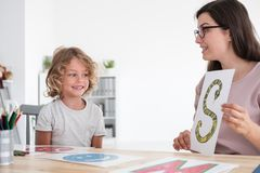 Speech therapist teaching pronunciation to a little kid using co royalty free stock photography
