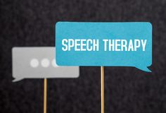 Speech therapy text on cardboard speech balloon or bubble. On wooden stick. Stuttering, lisp and learning to talk concept Royalty Free Stock Image