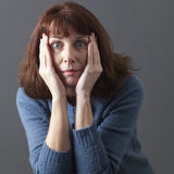 Speechless 50s woman expressing surprise and fear Stock Photos