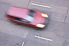 Speed. A bird's eye view of a street with a blur of a red vehicle driving down a lane with the headlights on royalty free stock image
