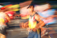 Speed. Marathon runners head into the sun during the early stages of a race royalty free stock image
