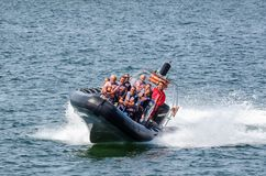 HOLIDAY AT THE SEASIDE. KOLOBRZEG., WEST POMERANIAN / POLAND - 2019: A crazy tourist ride by motorboat in the sea royalty free stock photo