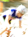 Speed. Male pro bicycle racer speeding by in a criterium - blurred image stock image