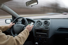 Driver using cell phone in car blurred motion Royalty Free Stock Photos