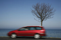 Speed along the coast. Speedy car along a coastal highway - Denmark  - at springtime Stock Photo