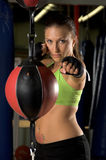 Speed Bag Jab. A beautiful young woman fighter training on a double ended bag in an MMA gym royalty free stock images