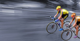 Speed bicyclists in motion, competition. Speedy bicyclists in motion, race, rally, monochrome background, competition Stock Image