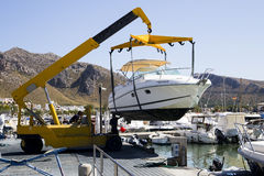 A speed boat being lowered into the sea by a crane Stock Photography