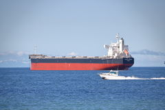 Speed Boat and Bulk Carrier Royalty Free Stock Photo