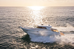 Speed boat in the ocean with sun setting behind Royalty Free Stock Image