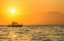 Speed boat in the ocean at sunrise. Silhouette of Speed boat in the ocean at sunrise. floating at sunset in Atlantic ocean, South Africa Royalty Free Stock Photos