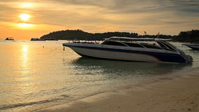 Speed boat parking on the beach at sunset Stock Photography