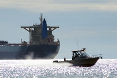 Speed boat passing in full speed in front of a trans-ocean conta. Iner ship tanker in Vancouver English Bay Royalty Free Stock Photos