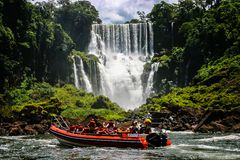 Speed boat rides under the water cascading over the Iguacu falls in Iguacu, Brazil stock photo