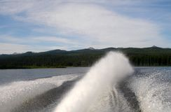Speed Boat Spray. Water spray form back of speed boat with mountains in background Stock Images