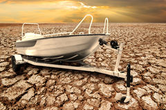 Speed boat on the trailer for transportation with oars on the dr. Y cracked earth in desert concept a symbol of global warming Stock Images