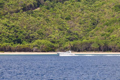Speed boat in the tropics. Large speed boat cruising along the shoreline of a tropical island Royalty Free Stock Images