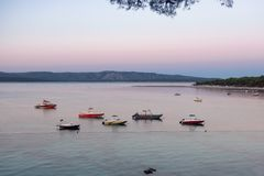 Speed boats floating on the calm sea, before the sun rises royalty free stock image
