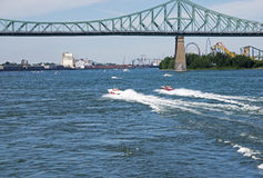 Speed boats on the St. Lawrence River. Power boats speeding towards the Jacques Cartier bridge in Montreal, Quebec, Canada Royalty Free Stock Photo