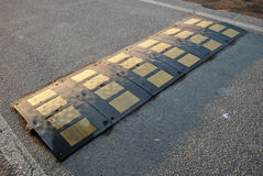 Speed bump. Old and uneven road speed bump during the sunset Stock Photo