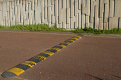Speed bump. A black and yellow speed bump, rumble strip stretches across a red tarmac road Stock Images