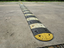 Speed bump on a concrete road. An old pale yellow and black traffic safety speed bump on a concrete road at parking lot royalty free stock image