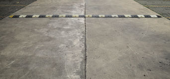 Speed bump on a concrete road. An old pale yellow and black traffic safety speed bump on a  concrete road at parking lot Stock Image
