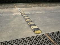Speed bump on a concrete road. An old pale yellow and black traffic safety speed bump on a  concrete road at parking lot Royalty Free Stock Photo