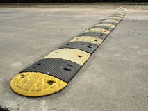 Speed bump on a concrete road. An old pale yellow and black traffic safety speed bump on a  concrete road at parking lot Stock Photography
