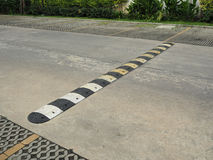Speed bump on a concrete road. An old pale yellow and black traffic safety speed bump on a  concrete road at parking lot Stock Photo