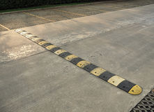 Speed bump on a concrete road. An old pale yellow and black traffic safety speed bump on a  concrete road at parking lot Stock Photos