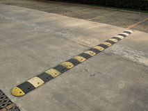 Speed bump on a concrete road. An old pale yellow and black traffic safety speed bump on a concrete road at parking lot stock images