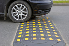 Speed bump on a road. And car Stock Photo
