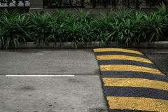 Speed bump on the road. Yellow and gray speed bump on the road for redcing speed stock images