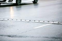 Speed bump on wet asphalt road Stock Photo