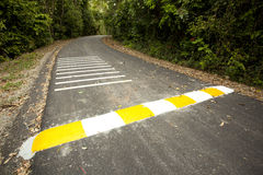 Speed bump. Yellow and white strip speed bump on road Royalty Free Stock Photo