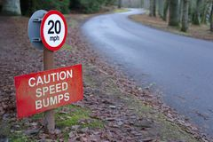 Speed bumps caution sign at road highway in countryside. Speed Bumps Caution 20 mph Sign in Rural Countryside Estate royalty free stock photos