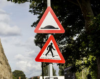 Speed bumps and pedestrian crossing. Sign on a post royalty free stock image