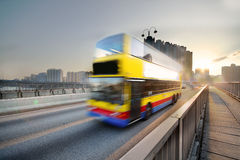 Speed bus through sunset road Stock Photos