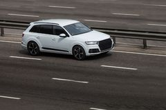 Audi white rides on the road. Against a background of blurred trees stock photos