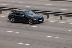 Luxury car black BMW  speeding on empty highway Stock Image