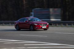 Luxury car red Mazda speeding on empty highway Royalty Free Stock Images