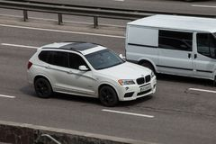 Luxury car white BMW speeding on empty highway Stock Photography