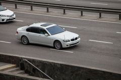 Luxury car white BMW 750 speeding on empty highway Royalty Free Stock Photos