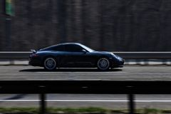 Porsche 911 Carrera black rides on the road. Against a background of blurred trees royalty free stock photos