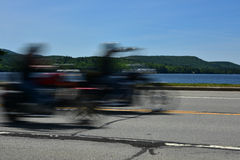 Speed concept - Motorcycles speeding past lake Stock Images