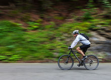 Speed cycling. Gourette, France- July 15th, 2011: Image of an amateur cyclist going down on the road to Col D'abisuqe,in Pyrenees Mountains, before passing the Royalty Free Stock Images