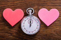 Speed Dating Concept. Hearts And A Stop Watch. Speed Dating Concept. Two Heart Shapes And A Stop Watch On Wooden Desk stock image